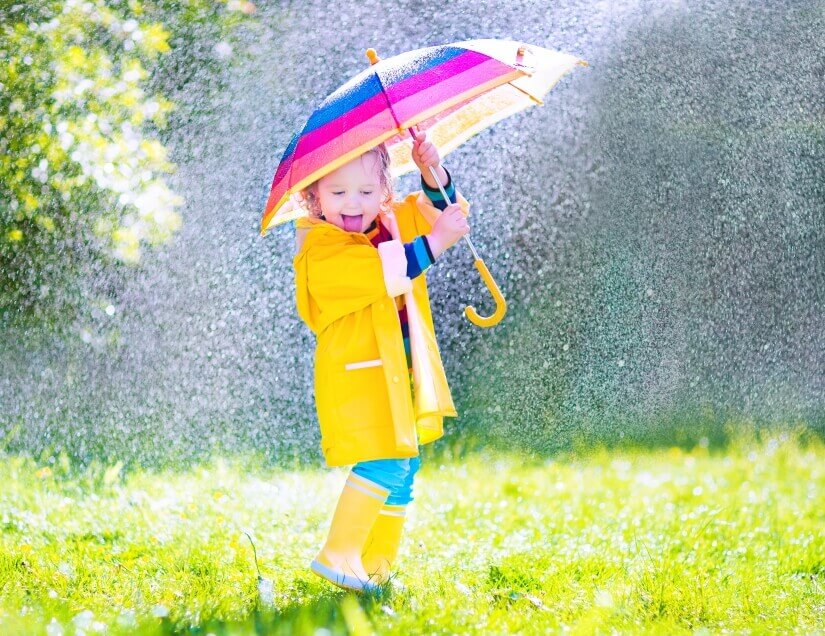 Mädchen im Regen mit Schirm