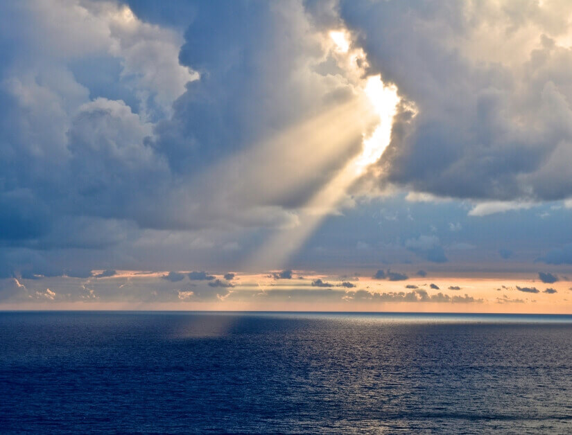 Licht durchbricht Wolkendecke über Wasser