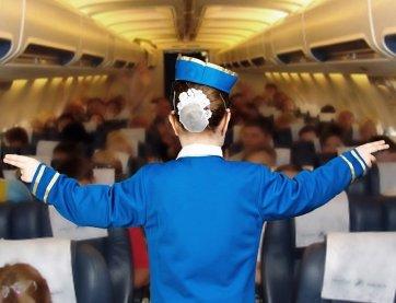 Stewardess zeigt die Notausgänge