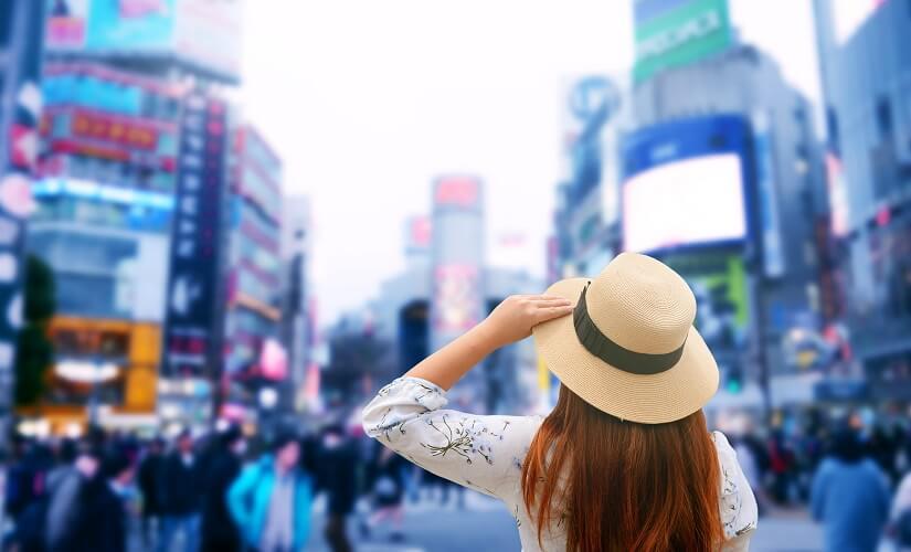 Eine Touristin steht an der Shibuya-Kreuzung in Tokio