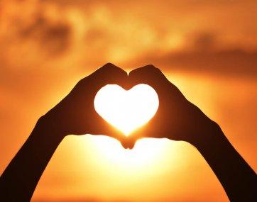 Zwei Hände formen ein Herz vor einem Sonnenuntergang