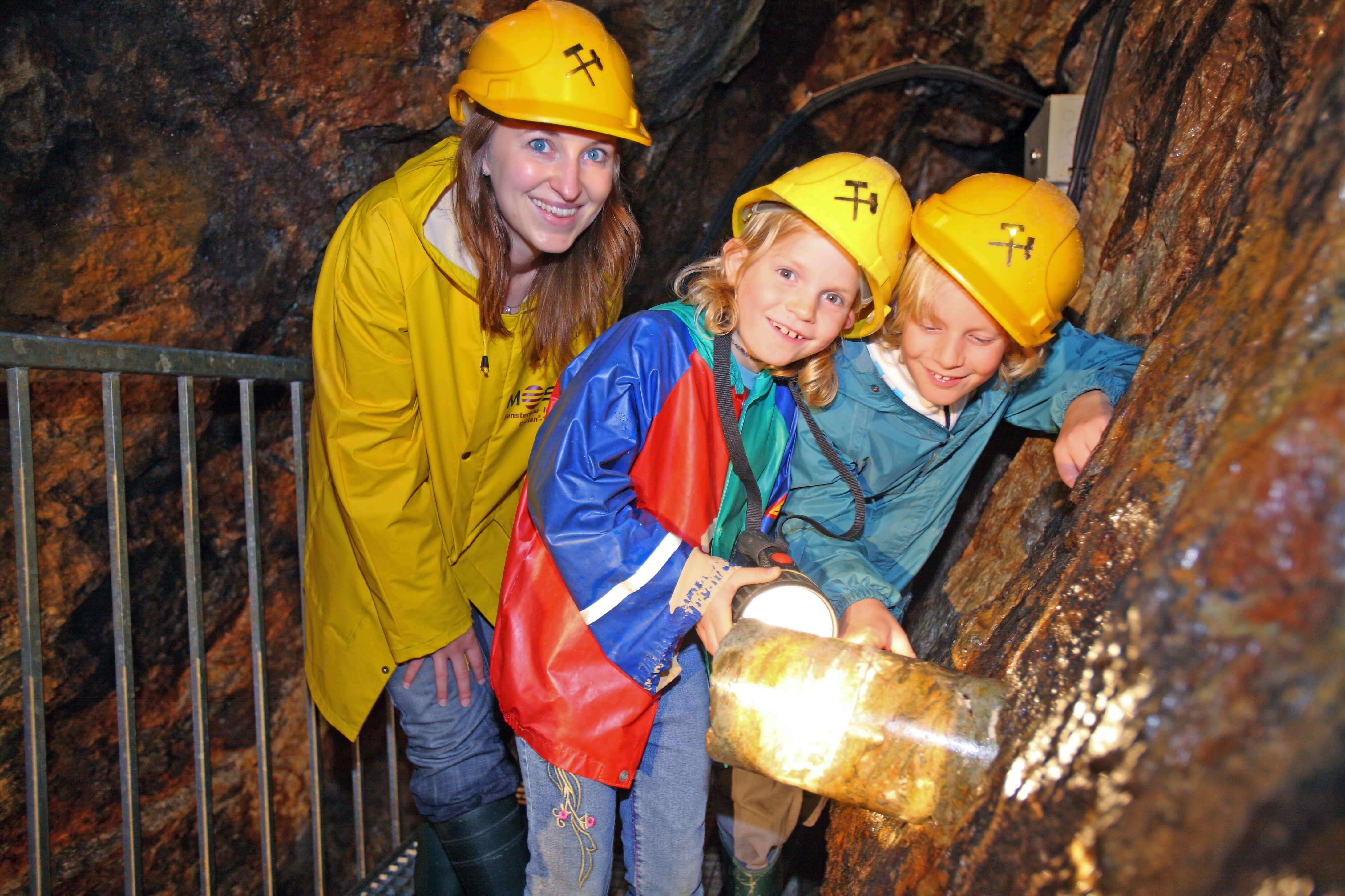 Kinder zu Beusch im Bergwerk, Bergwerksführer bei der Arbeit, Höhle, Bergwerk, Tropfsteine, Helm, Arbeitsjacke, Kinder
