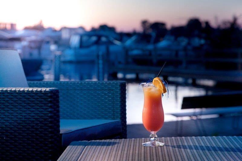 Cocktail im Skippers am Wasser auf einem Tisch und Rattansessel