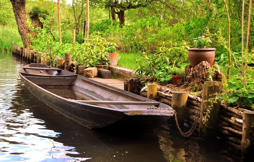 Boot am Steg auf einem Fluss im Wald