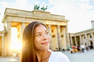 Berlin people - woman at Brandenburg Gate or Brandenburger Tor, smiling happy in Berlin, Germany. Beautiful multiracial Asian Caucasian woman looking to side during travel in Europe.