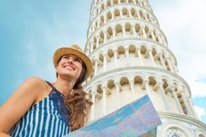 Happy young woman with map in front of leaning tower of pisa, tuscany, italy