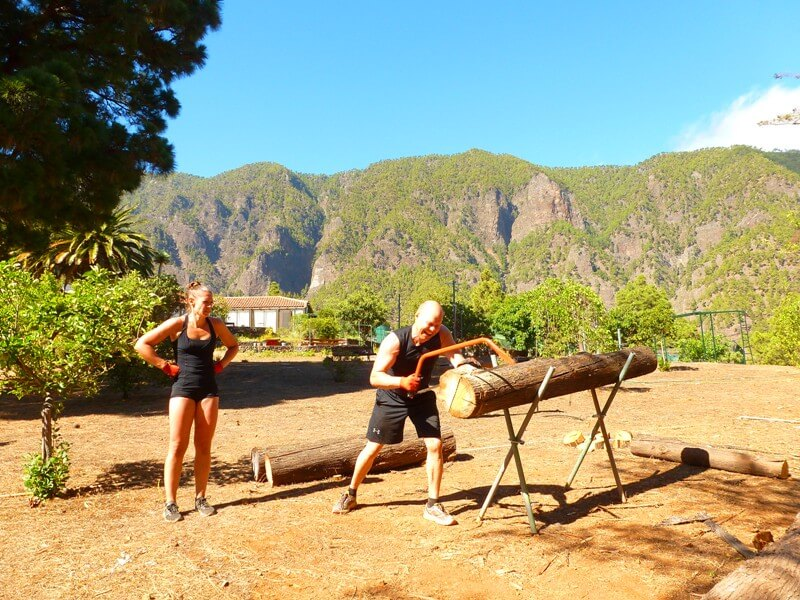 Mann Frau sägen Baumstamm Fitness mal anders- im Nature Fitness Camp