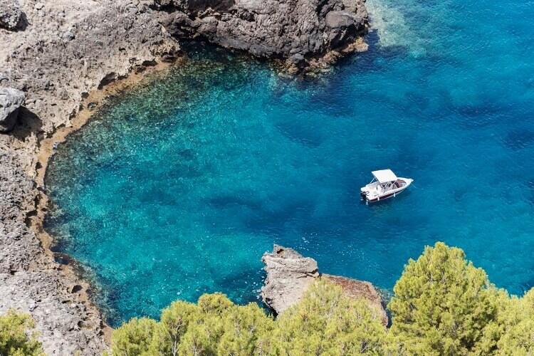 Blick von Oben auf ein Boot in einer Bucht, Ibiza, Spanien