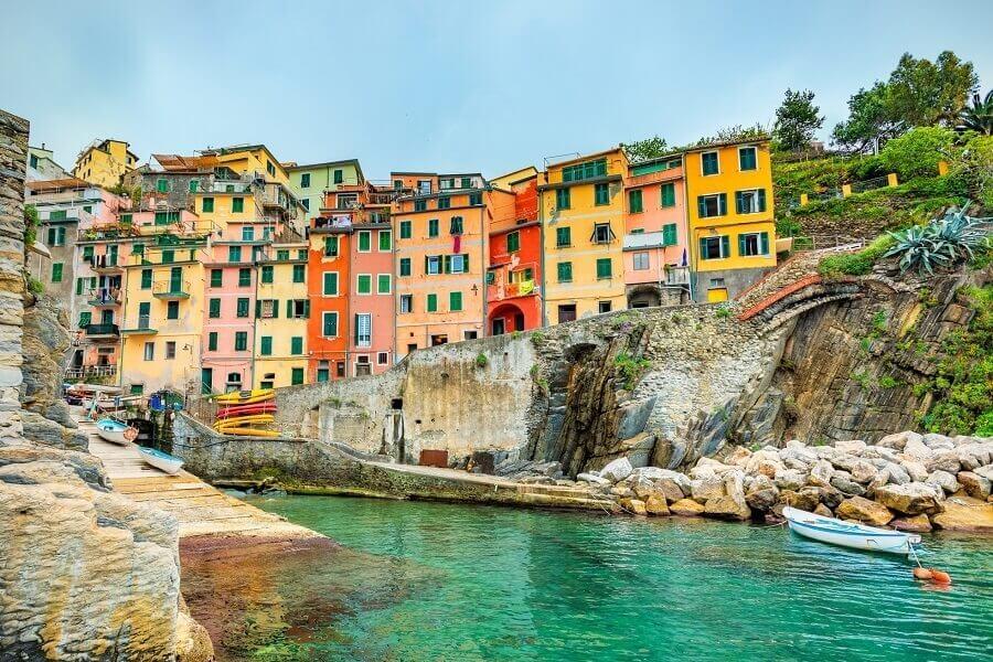 Blick vom Wasser aus auf bunte Häuser, Riomaggiore, Italien