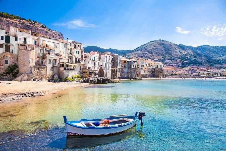 Kleines Boot am Strand von Sizilien, im Hintergrund ein Dorf