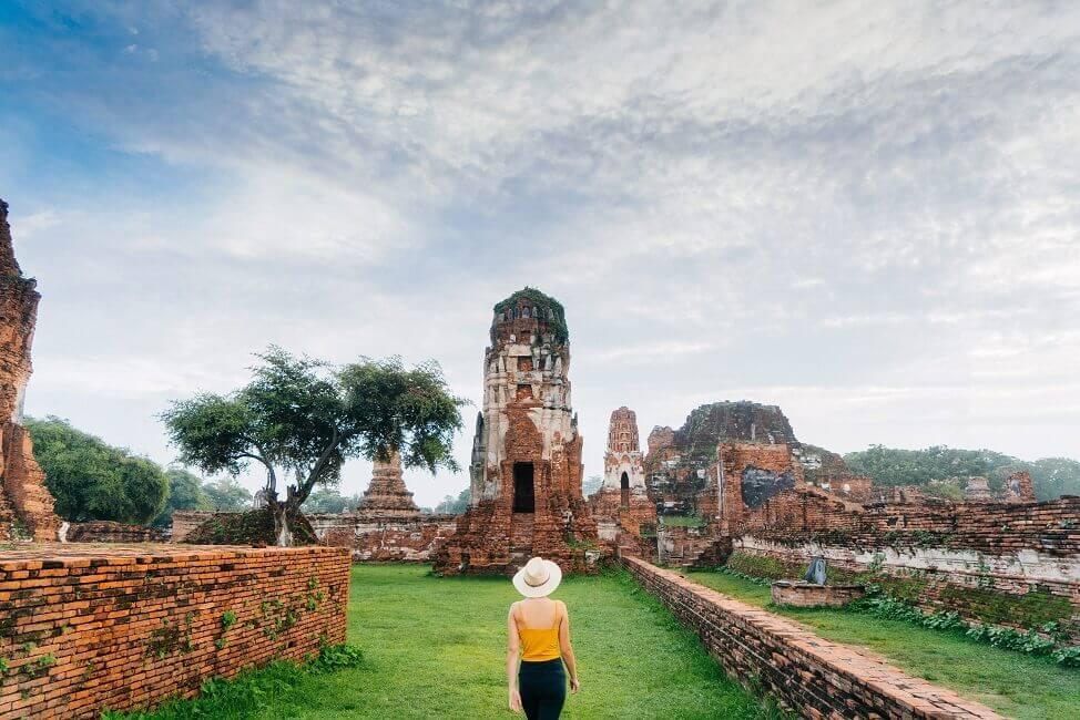 Buddhistischer Tempel in Ayutthaya mit Frau davor