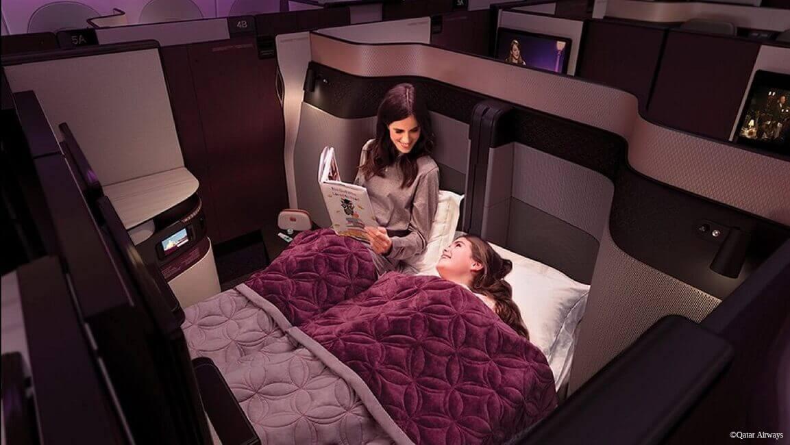 Frau und Tochter liegen im Bett in der ersten Klasse, Flugzeug