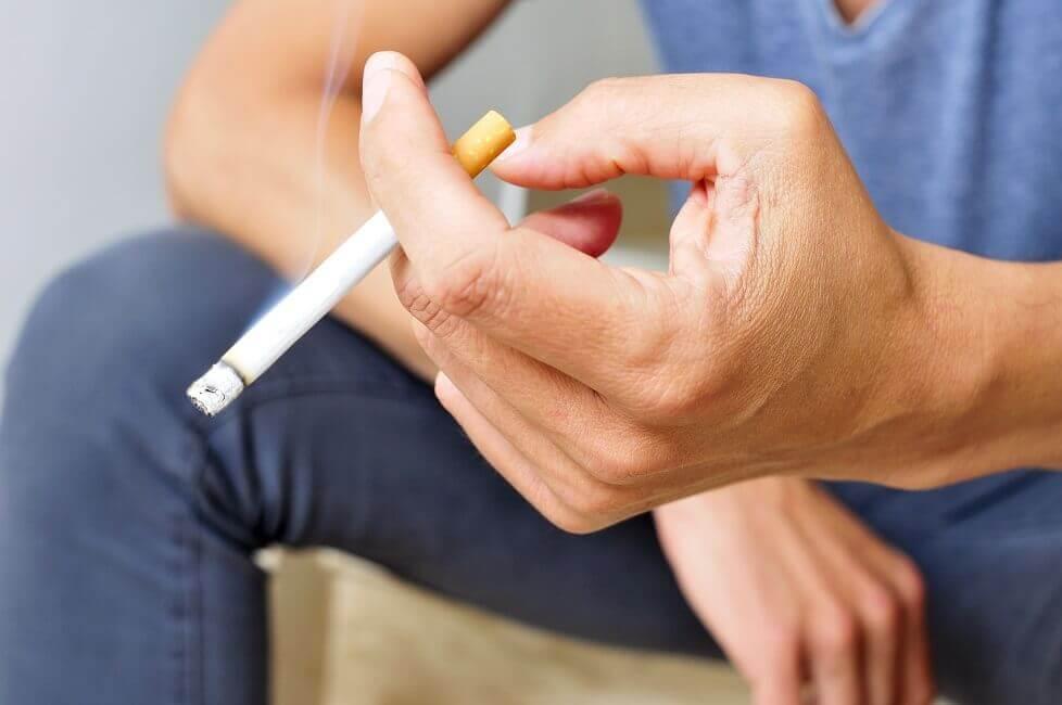 brennende Zigarette in der Hand