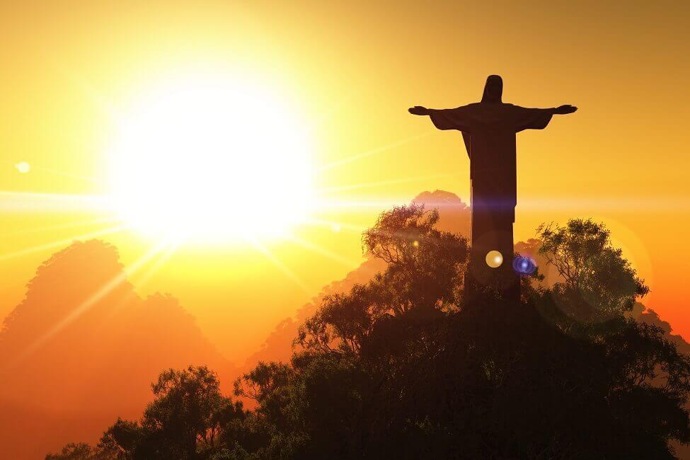 In den Abendstunden steht die Sonne hinter der Figur, die einen langen Schatten auf Rio wirft.