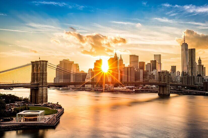 Die Sonne scheint durch die Wolkenkratzer von Manhattan auf die Brooklyn Bridge und den East River.