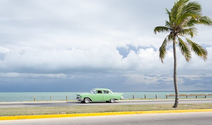 Oldtimer an einer Küstenstraße auf Kuba