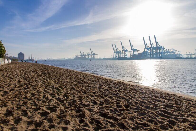 Elbstrand von Hamburg mit Hafenkränen am anderen Ufer