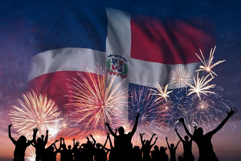 Menschen feiern bei einem Feuerwerk, im Hintergrund ist die Flagge der Dominikanischen Republik zu sehen
