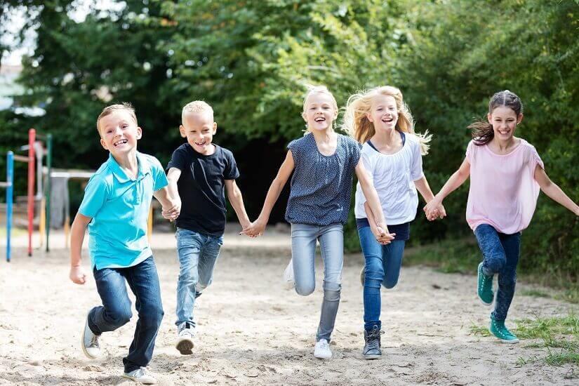 Mädchen und Jungen laufen Hand in Hand über einen Spielplatz