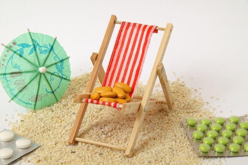 Miniatur Sonnenstuhl mit Sonnenschirm und Tabletten