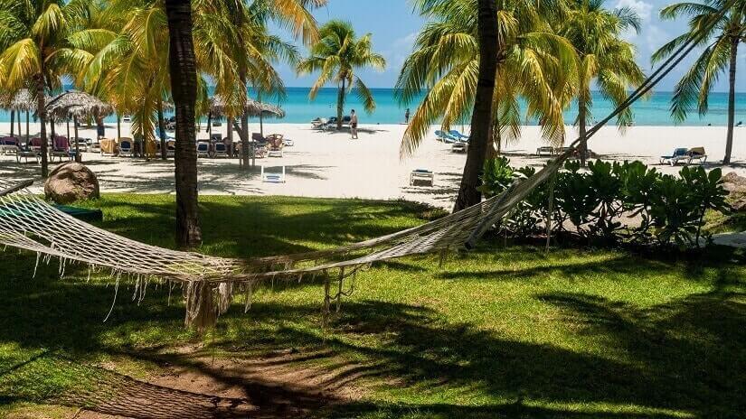 Palmen, Rasen, weißer Sand und türkisfarbenes Meer auf Kuba