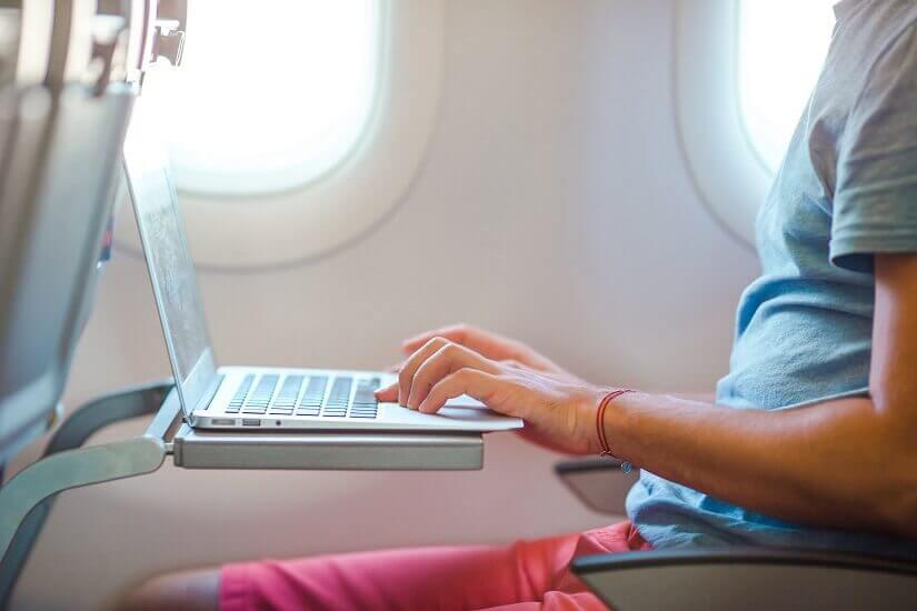 Mann im Flugzeug nutzt sein Notebook