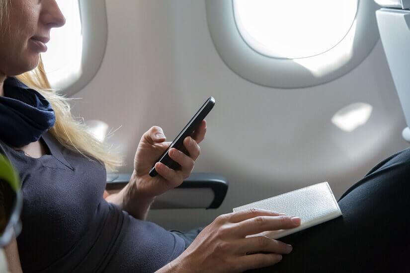 Eine Frau nutzt ihr Mobiltelefon im Flugzeug