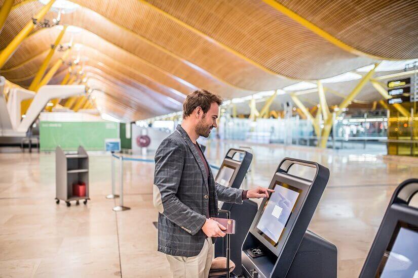 Ein Mann checkt am Flughafen im Automaten ein.