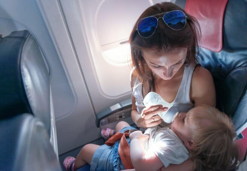 Mutter gibt Säugling das Fläschchen im Flugzeug