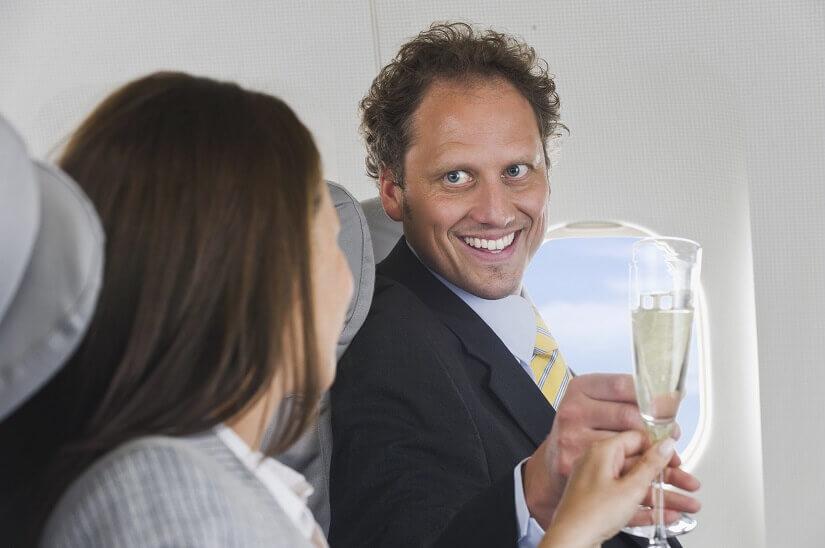 Ein Mann und eine Frau prosten sich im Flugzeug mit Sekt zu