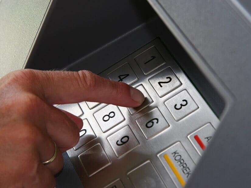 Kunde gibt PIN am Geldautomaten ein