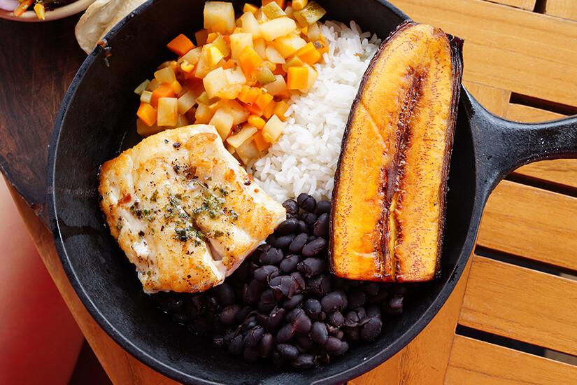 Traditionelles Gericht mit Reis, Bohnen, Fisch und Kochbanane