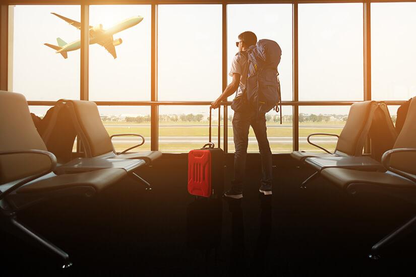 Mit Koffer und Rucksack am Flughafen