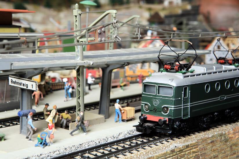Miniatur Eisenbahn fährt in den Bahnhof ein