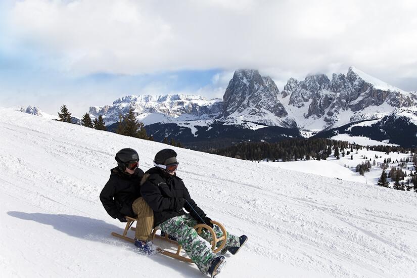 Mit dem Schlitten die Berghaenge der Dolomiten hinuntersausen