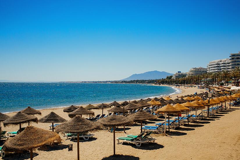 Sonnenliegen am Strand von Marbella